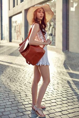 Fashionable brunette woman in a white dress, straw hat, walking in the street, posing near shop windows