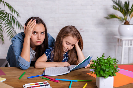 Photo pour Mother becoming frustrated with daughter whilst doing homework sitting at the table at home in learning difficulties homework. - image libre de droit