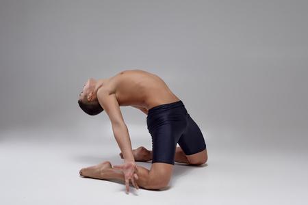 Photo pour Photo of a handsome man ballet dancer, dressed in a black shorts, making a dance element against a gray background in studio. - image libre de droit