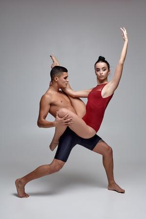 Photo pour The couple of an athletic modern ballet dancers are posing against a gray studio background. - image libre de droit