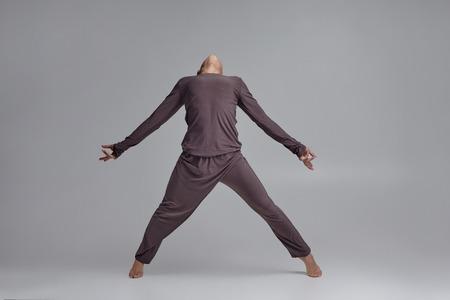 Foto de Photo of an athletic man ballet dancer dressed in a gray tracksuit, making a dance element against a gray background in studio. - Imagen libre de derechos