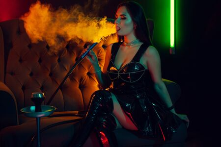 Photo for Sexy brunette model is smoking a hookah exhaling a smoke at a luxury night club. - Royalty Free Image