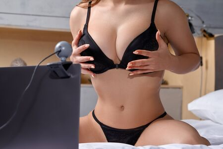 Foto de Beautiful, young girl posing in front of a web camera, working as a model. He takes off his bra. The concept of online flirting, sex on the Internet. - Imagen libre de derechos