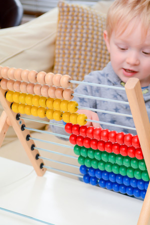 Foto de Child learning to count. Young boy using an abacus to learn maths - Imagen libre de derechos