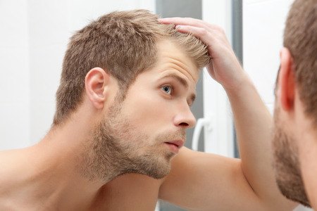 Photo for Handsome unshaven man looking into the mirror in bathroom - Royalty Free Image