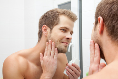 Photo pour Man looking into the mirror and applying aftershave - image libre de droit