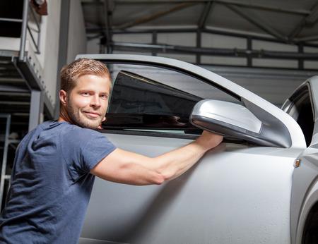 Foto de Applying tinting foil onto a car window in a workshop - Imagen libre de derechos