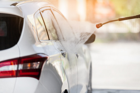 Foto de Cleaning the car with the high pressure car wash washer - Imagen libre de derechos