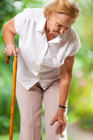 Photo pour Elderly woman in the 80s with a walking stick - image libre de droit