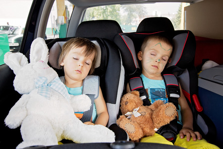 Photo for Two boys in car seats, travelling, sleeping in the car with teddy bears - Royalty Free Image