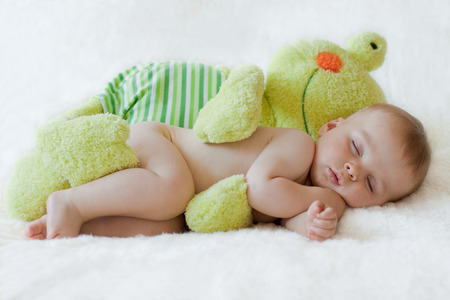 Photo pour Little baby boy, sleeping with frog toy - image libre de droit