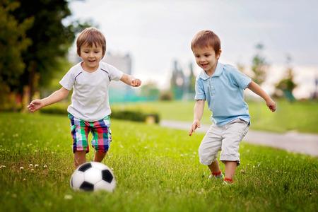 Foto de Two cute little boys, playing football - Imagen libre de derechos