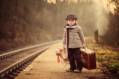 Foto de Adorable boy on a railway station, waiting for the train with suitcase and teddy bear - Imagen libre de derechos