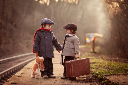 Photo pour Two boys on a railway station, waiting for the train with suitcase and teddy bear - image libre de droit