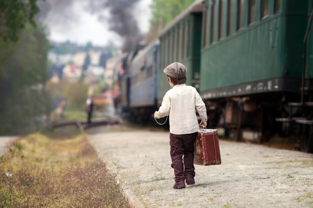 Foto per Boy, dressed in vintage shirt and hat, with suitcase, on a railway station, steam train - Immagine Royalty Free