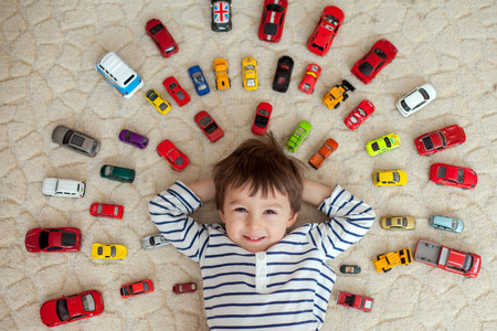 Photo pour Adorable boy, lying on the ground, toy cars around him , looking at the camera, shot from above - image libre de droit