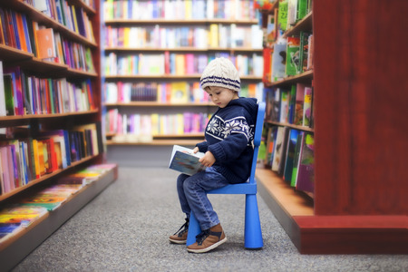Foto de Adorable little boy, sitting in a book store, looking at books - Imagen libre de derechos