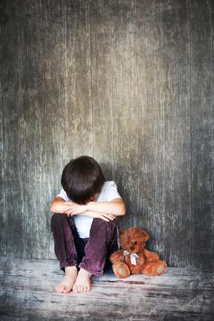 Foto de Young boy, sitting on the floor, teddy bear next to him, crying, looking away - Imagen libre de derechos