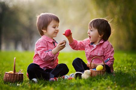 Foto de Two boys in the park, having fun with colored eggs for Easter - Imagen libre de derechos