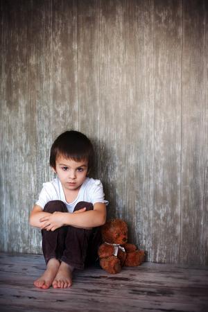 Foto de Young boy, sitting on the floor with his teddy bear, sadness in his eyes - Imagen libre de derechos