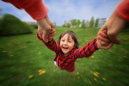 Photo pour Mother, spinning in circle her little baby boy, pure joy, radial blur, springtime, daytime - image libre de droit