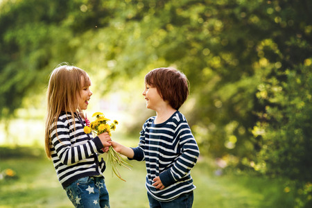 Photo for Beautiful boy and girl in a park, boy giving flowers to the girl. Friendship concept - Royalty Free Image