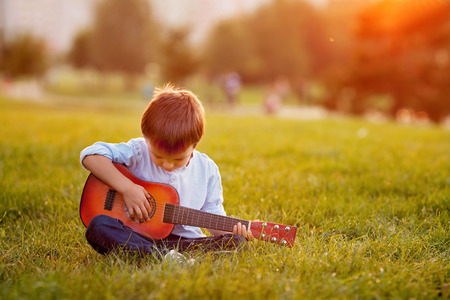 Photo for Adorable boy with guitar, sitting on the grass on sunset - Royalty Free Image