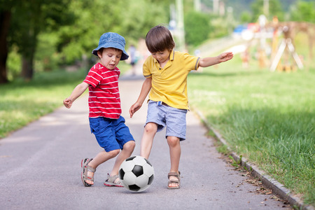 Photo for Two cute little kids, playing football together, summertime. Children playing soccer outdoor - Royalty Free Image