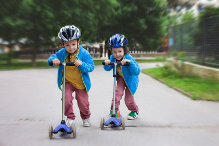 Photo pour Two cute boys, compete in riding scooters, outdoor in the park, summertime - image libre de droit