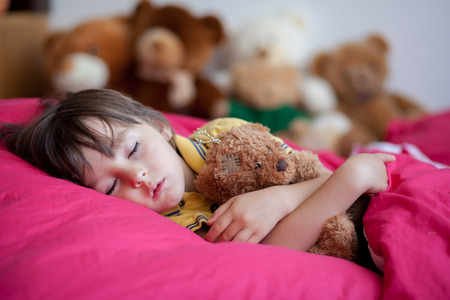 Photo pour Sweet little boy, sleeping in the afternoon with his teddy bear toy - image libre de droit