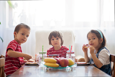 Photo pour Three happy kids, two brothers and little sister, having healthy breakfast sitting at wooden table in sunny kitchen - image libre de droit