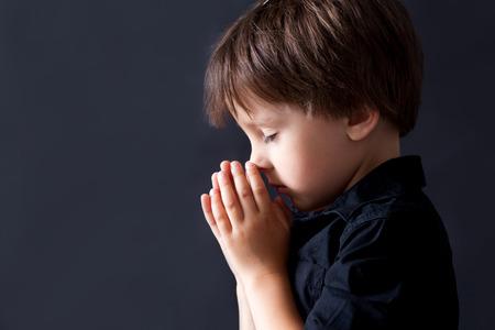 Foto de Little boy praying, child praying, isolated black background - Imagen libre de derechos