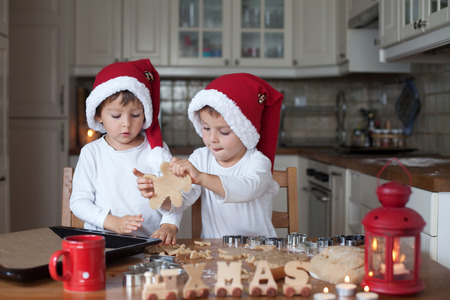 Photo pour Two cute boys with santa hat, preparing cookies in the kitchen at home - image libre de droit