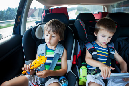 Foto de Two boy in children car seats, traveling by car and playing with toys and tablet, summertime - Imagen libre de derechos