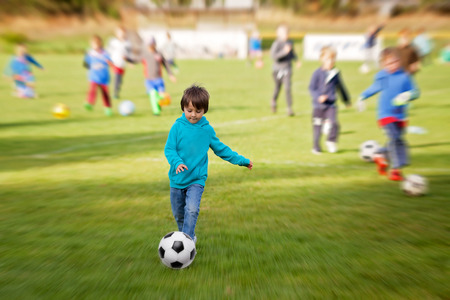 Photo pour Group of children, playing football, exercising outdoor, radial blur applied - image libre de droit