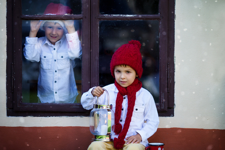 Two cute boys, brothers, one sittng on a window shield, the other looking through the window, behind him, holding cups with tea, waiting for Santa