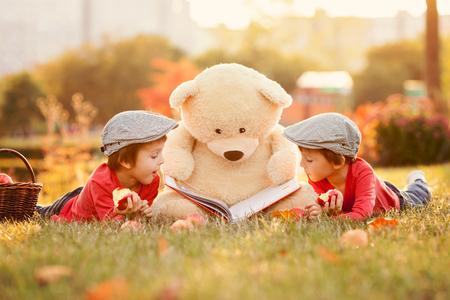 Photo pour Two adorable little boys with teddy bear friend in the park on sunset, nice back light - image libre de droit