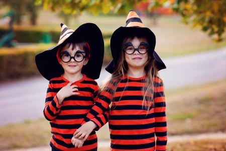 Foto de Boy and girl in the park in halloween costumes, having fun autumn time - Imagen libre de derechos