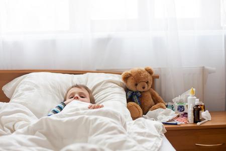 Foto de Sick child boy lying in bed with a fever, resting at home - Imagen libre de derechos