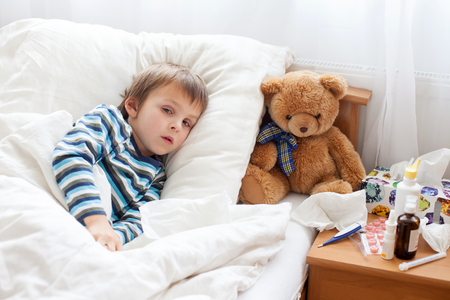 Foto de Sick child boy lying in bed with a fever, resting at home - Imagen libre de derechos