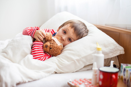 Foto de Sick child boy lying in bed with a fever, holding terry bear with band aid, resting - Imagen libre de derechos