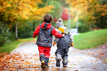 Foto de Two children, fighting over toy in the park on a rainy day, autumn time - Imagen libre de derechos