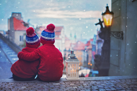 Photo pour Two cute kids, boys, standing on stairs, holding a lantern, view of Prague behind them, snowy evening - image libre de droit
