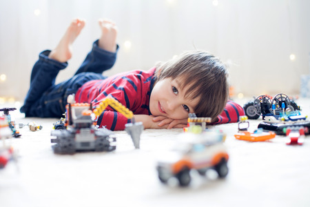 Photo pour Little child playing with lots of colorful plastic toys indoor, building different cars and objects - image libre de droit