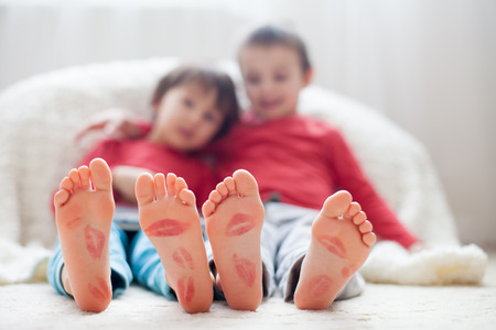 Photo for Little kids feet, covered with prints from kisses, children playing on tablet - Royalty Free Image