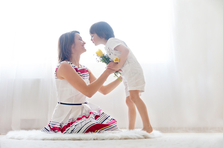 Photo for Mother and her child, embracing with tenderness and care, child  giving mother flowers. Mother day concept, happiness and love - Royalty Free Image