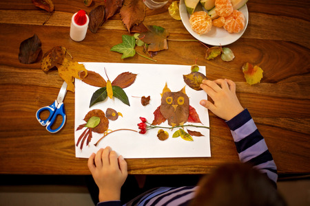 Foto de Sweet child, boy, applying leaves using glue while doing arts and crafts in school, autumn time - Imagen libre de derechos