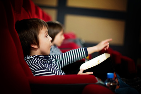 Photo for Two preschool children, twin brothers, watching movie in the cinema, eating popcorn - Royalty Free Image