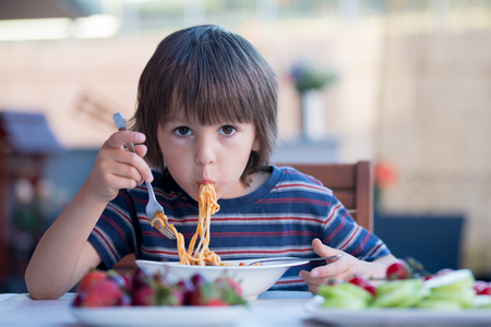 Photo for Cute child, preschool boy, eating spaghetti for lunch outdoors in garden, summertime - Royalty Free Image