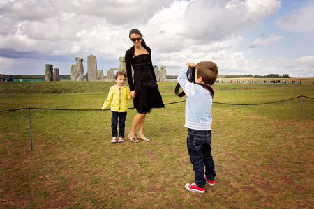 Photo for Young child, boy, taking pic of his mom and brother with digital camera at Stonehenge, family happiness concept - Royalty Free Image